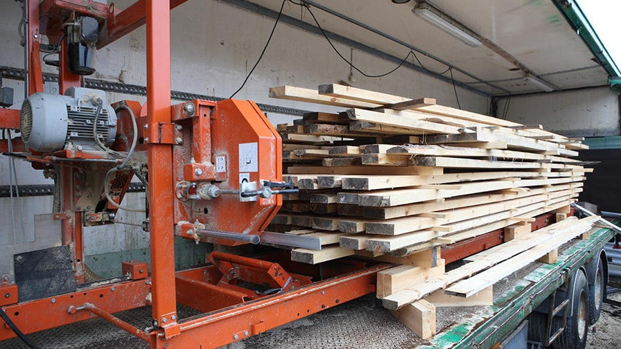 To make his sawmill easily movable, John´s solution was to to put the whole thing on wheels, into a truck container